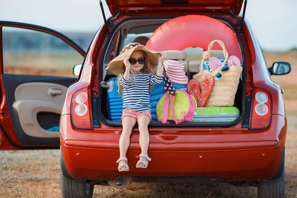 Traveling with young children, a picture of a little girl sitting on the opened trunk of a loaded up car holding on to her hat.