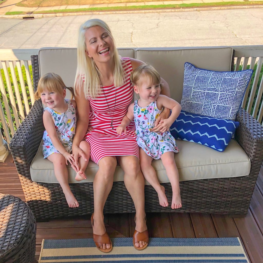 Mom of twins sitting on porch with twin girls.