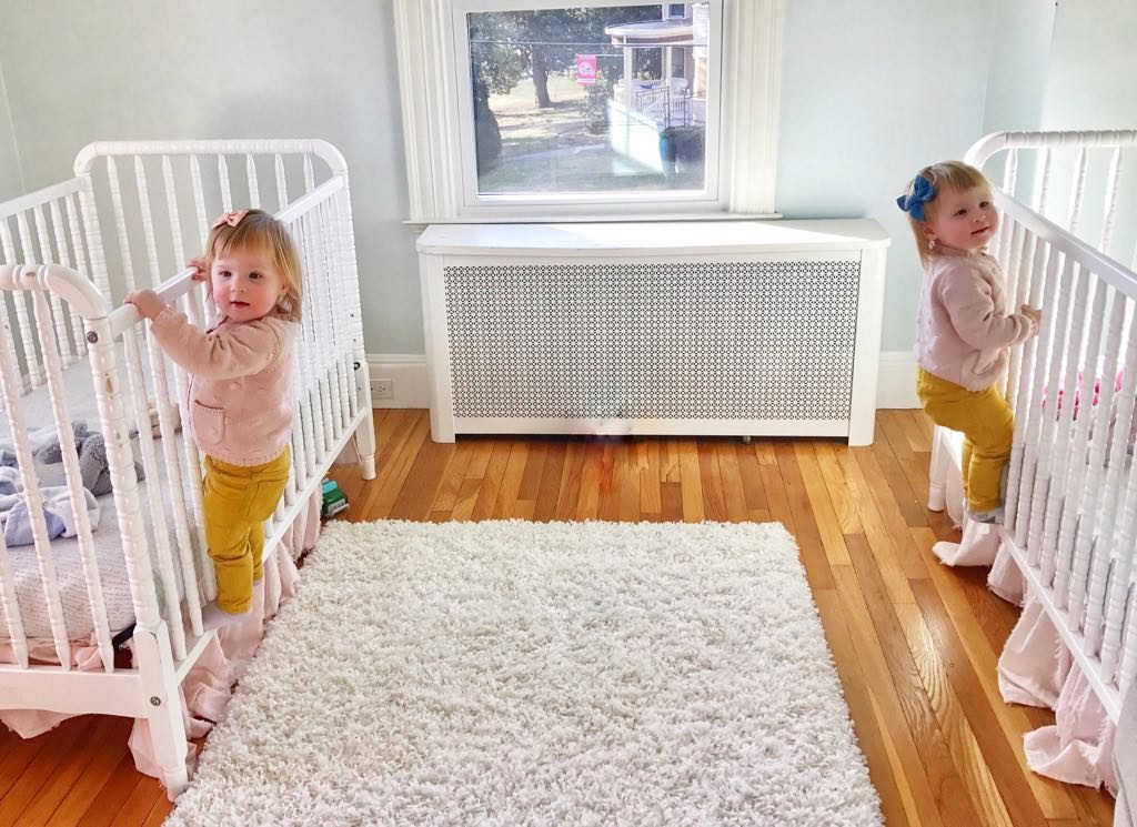 Twin girls climbing out of cribs.