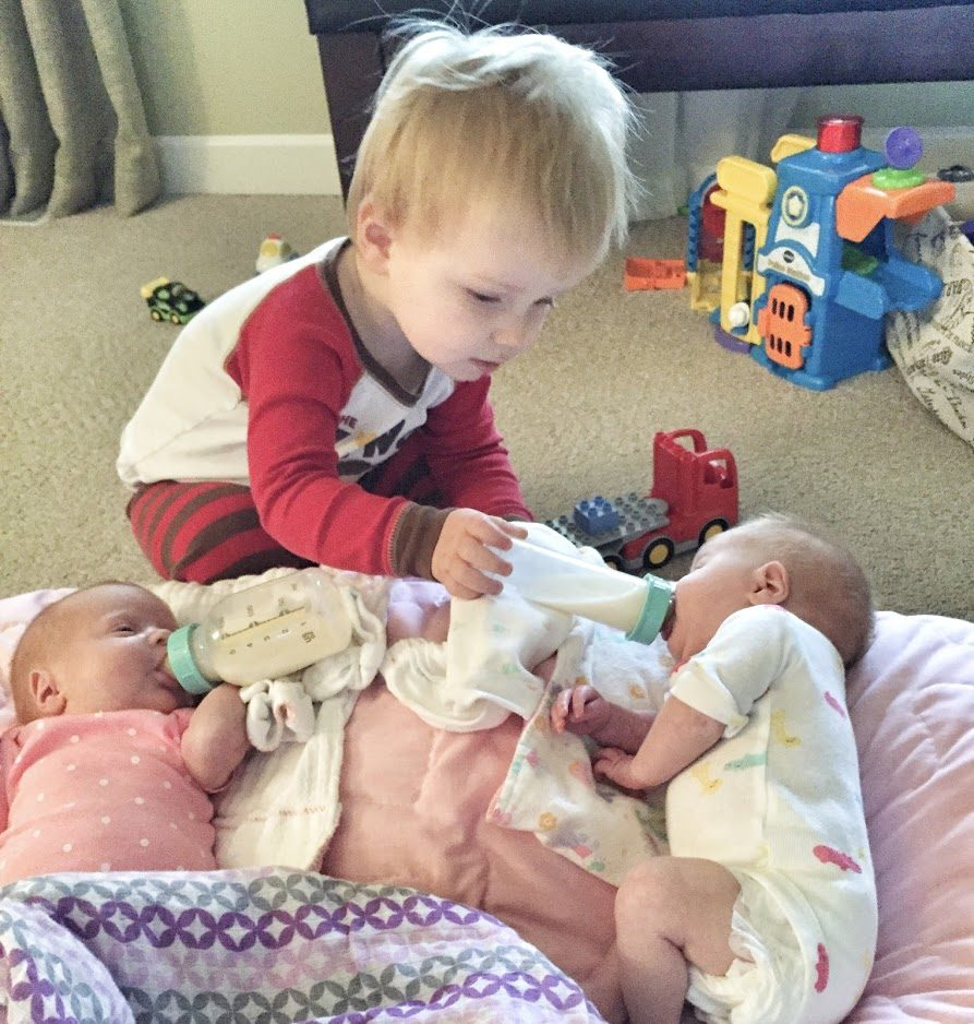 newborn twins and a toddler brother feeding them a bottle. 3 kids under 3.