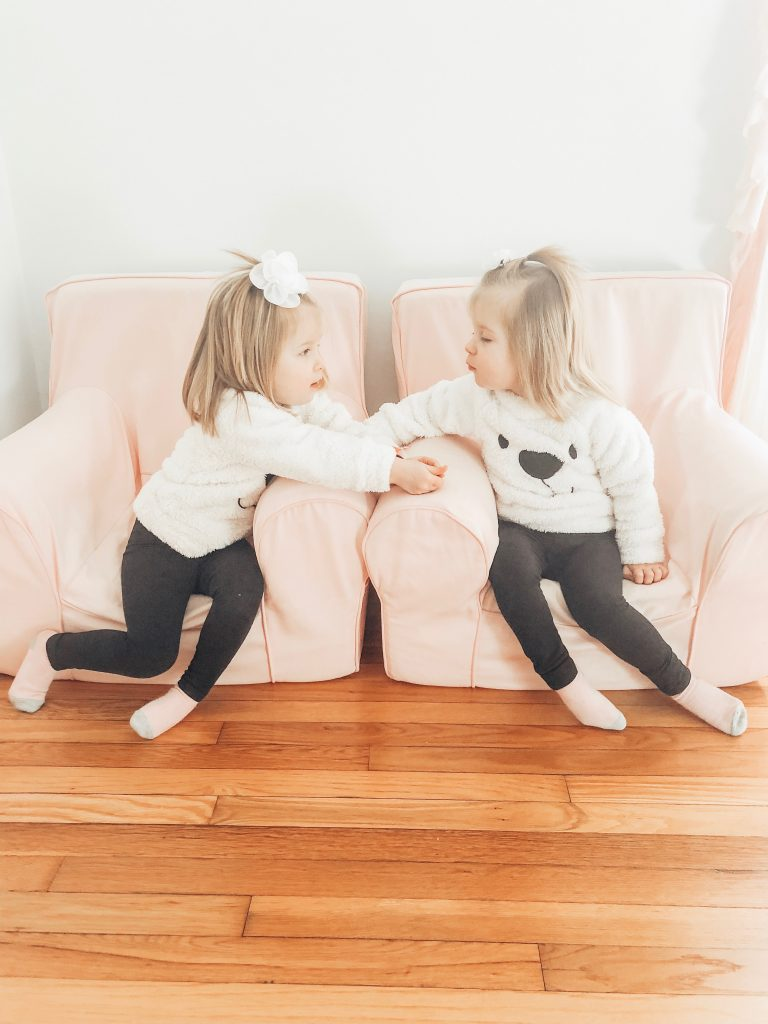 Identical toddler twin girls sitting in little pink chairs, staring into each others eyes.