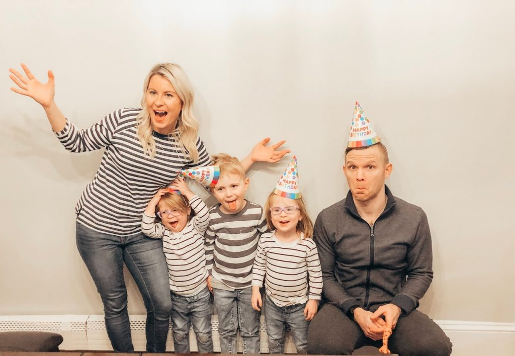 Picture of parents with identical three year old twin girls and 5 year old boy wearing birthday hats.