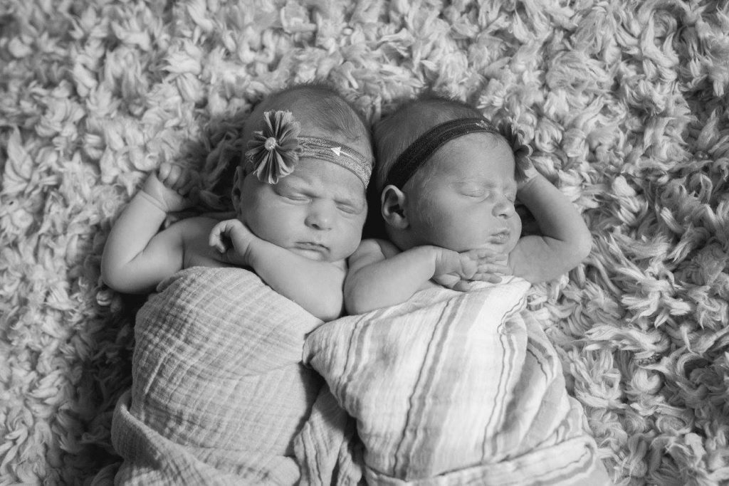 black and white picture of identical twin newborn girls sleeping. They are wearing headbands and wrapped in blankets.