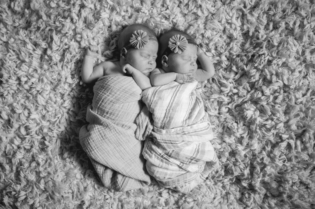 Black and white picture of newborn twin girls wrapped in blankets in identical poses.
