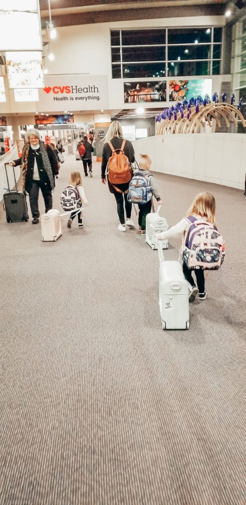 Mom with 3 kids going through airport.
