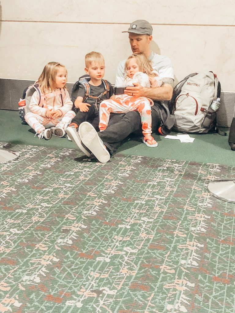 Father with twin girls and a little boy sitting on the airport floor showing them something on his phone.