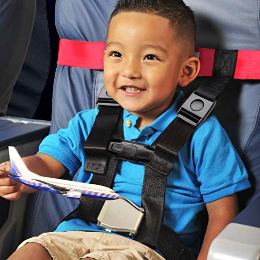 Traveling with young children, picture of a little boy traveling on airplane all buckled up.