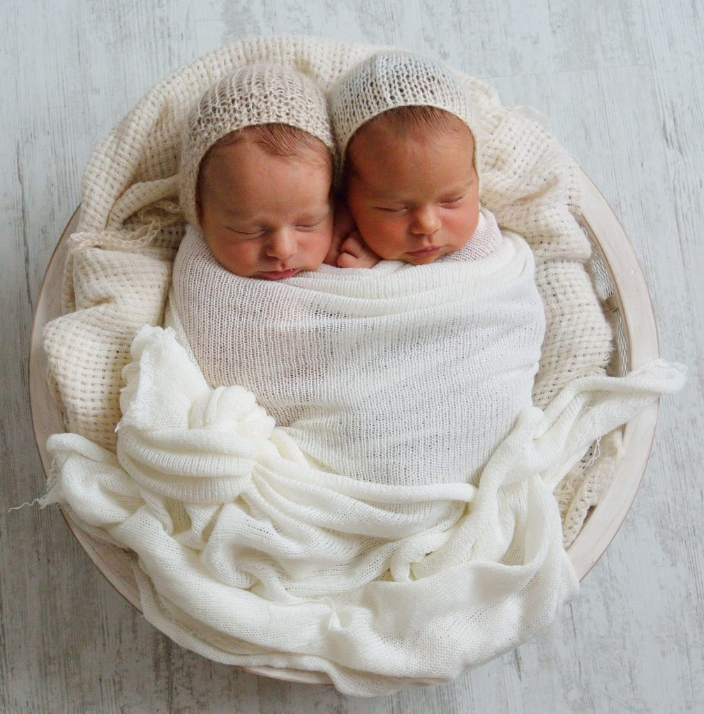 Sleeping newborn twins in a basket with swaddle and hats