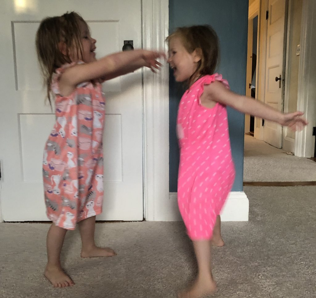 Identical preschool aged twin girls in night gowns about to hug.
