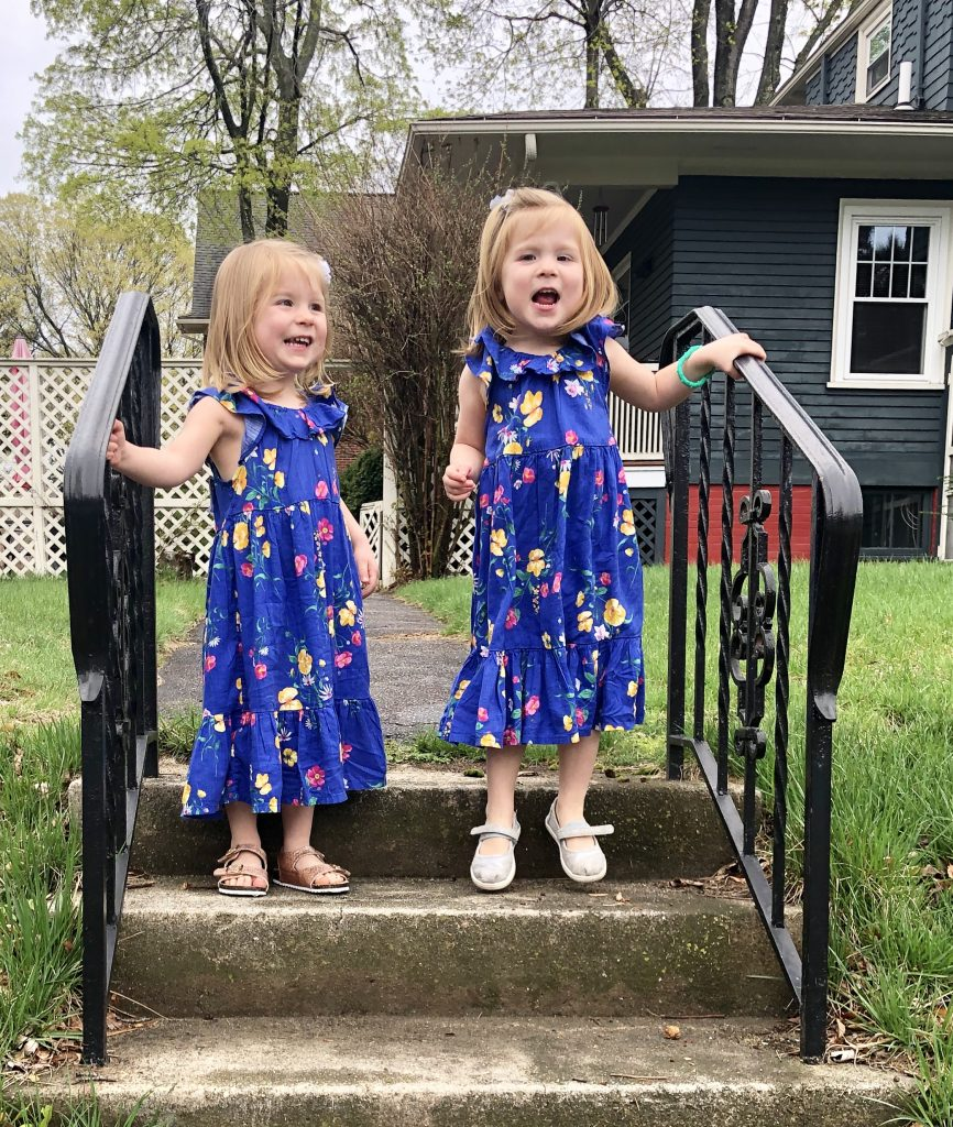 Identical three year old twin girls in flower dresses standing outside on stairs.