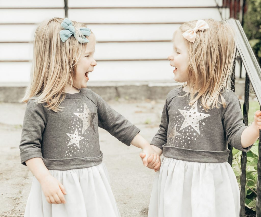 Identical three year old twin girls in star dresses, holding hands and laughing.