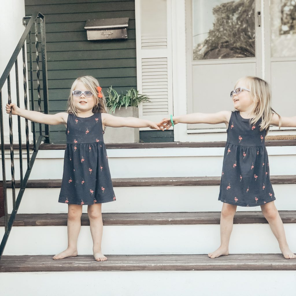 Identical twin girls in navy blue dresses with hot pink flamingos. Girls are standing on porch stars holding hands. They are also wearing purple glasses.