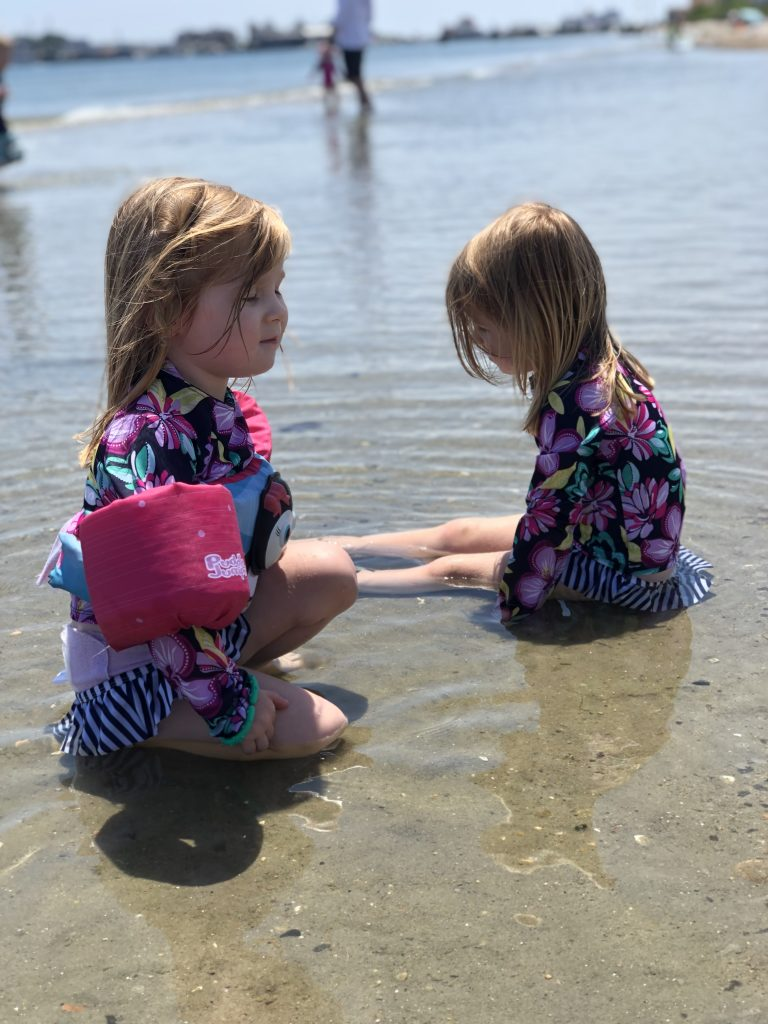 Identical preschool aged twin girls in bathing suits sitting in a pond facing each other.