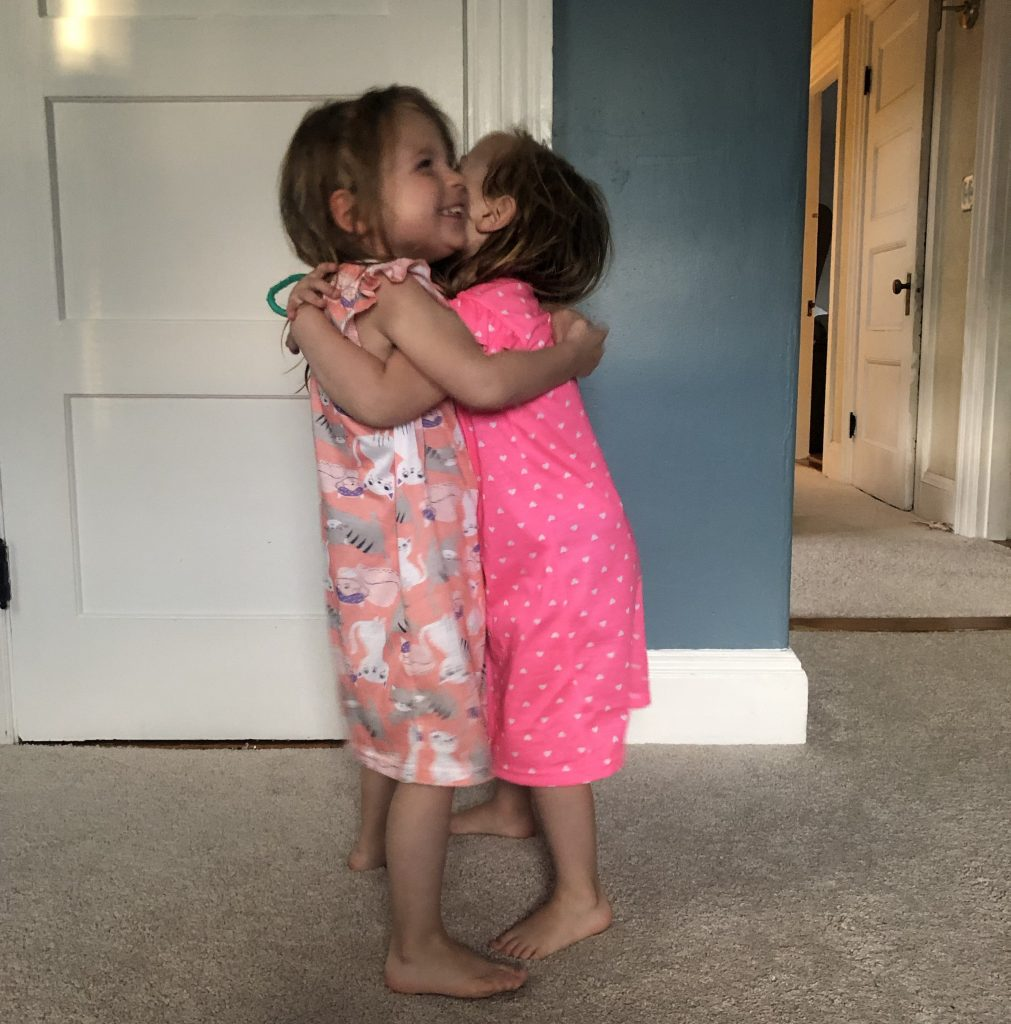 Identical preschool aged twin girls in nightgowns giving a big hug.