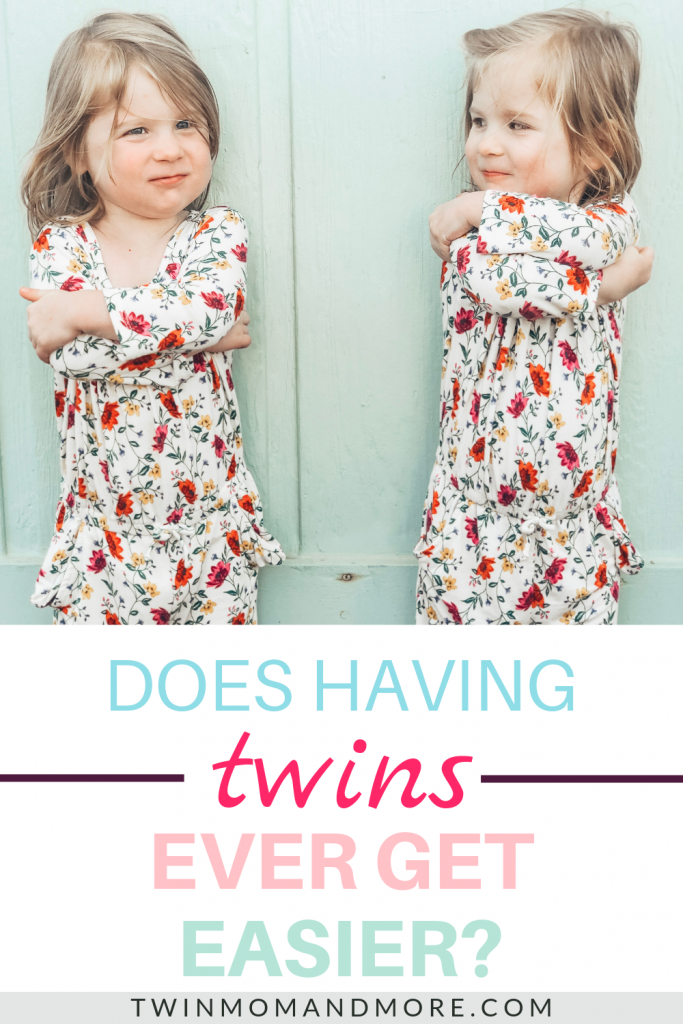 Pinterest image with text: does having twins ever get easier? Picture of identical twin toddler girls in floral rompers, crossing their arms and pouting at each other.