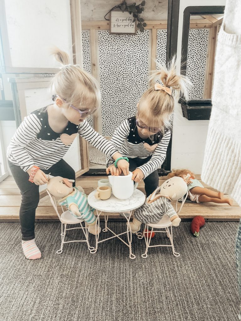 Identical twin toddlers playing dolls together.