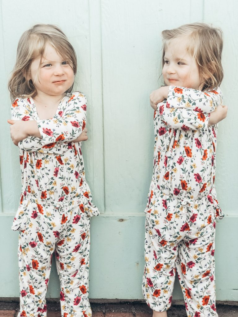 identical twin toddler girls in floral rompers, crossing their arms and pouting at each other.