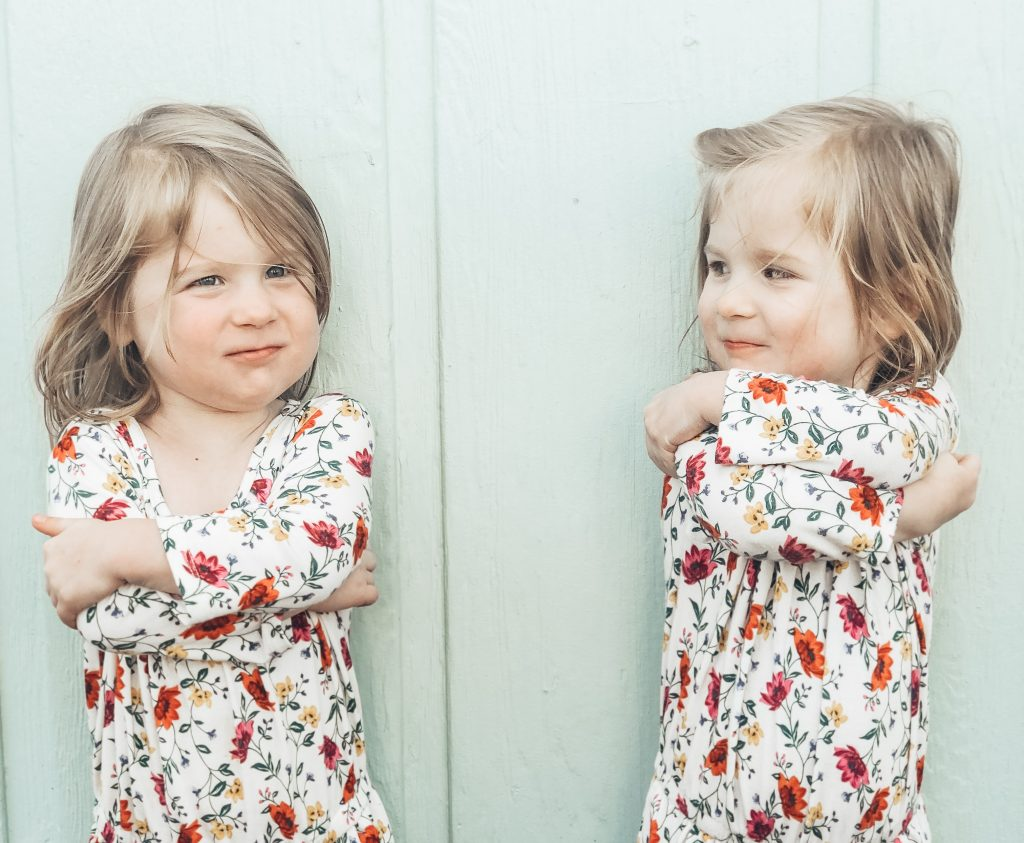 Identical three year old girls crossing their arms and looking at each other with sass.
