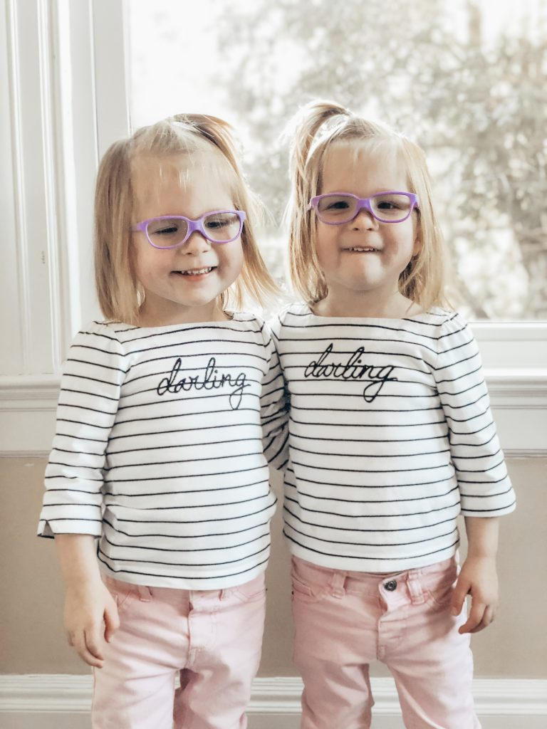 Identical twin three year old girls wearing purple glasses with their arms around each other.
