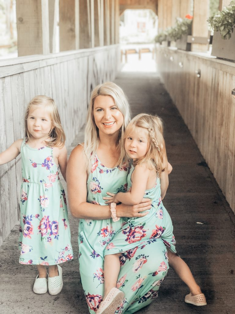 Mom of twins with identical twin girls in flower dresses smiling.