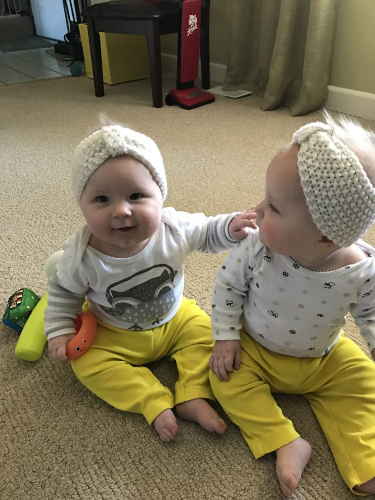 Identical twin baby girls with yellow pants playing together.