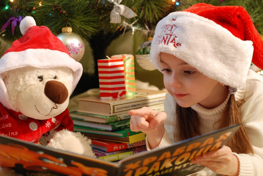 Little girl sitting under a Christmas tree reading a book.