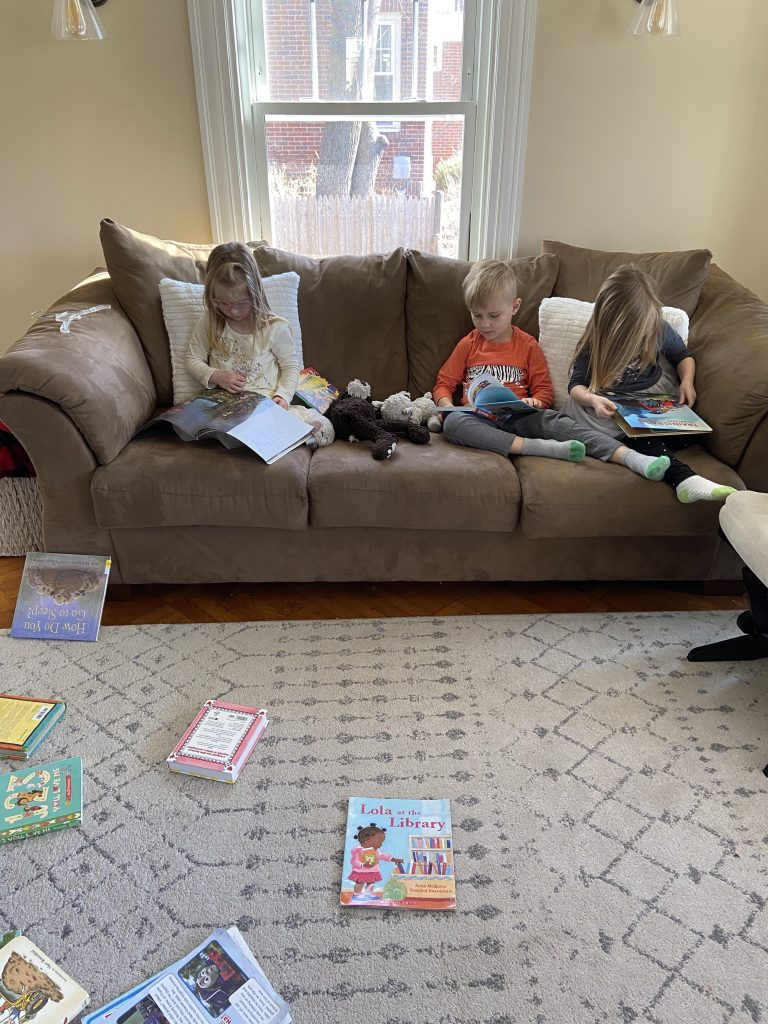3 children reading on a couch.