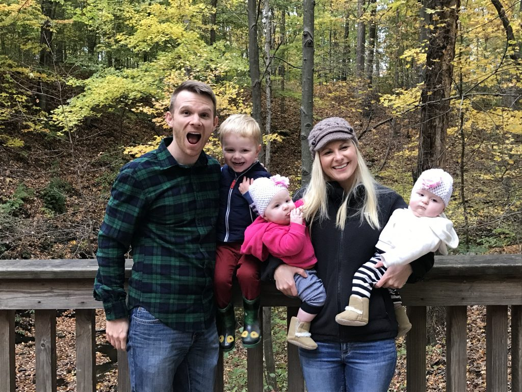 A family of 5 with a toddler and twin girls posing in the woods in the fall. 3 kids under 3.