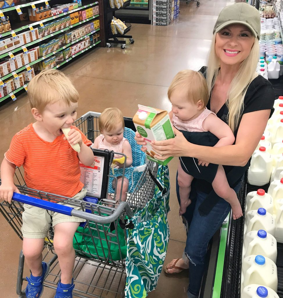 A mom at the grocery store wearing a baby with 2 other young children in the cart. The 3 kids are all under the age of 3, with a toddler boy and baby twin girls.