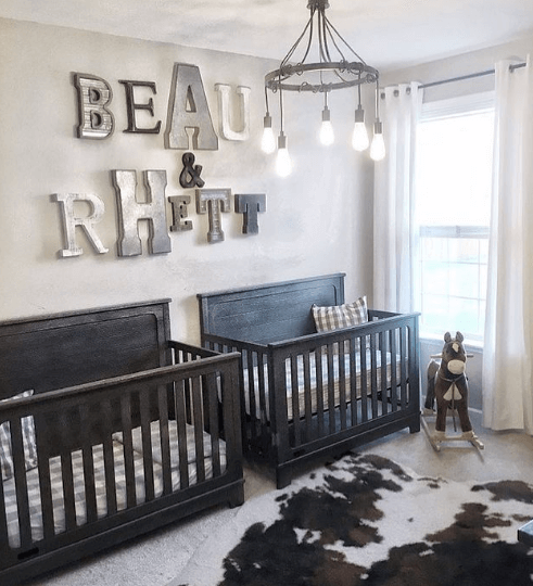 Rustic twin boy nursery with dark wooden cribs.