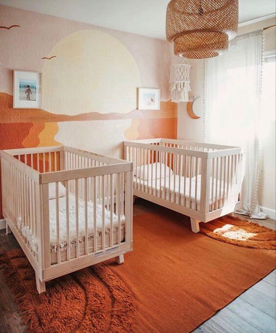 Gender neutral twin nursery with a sunset mural.