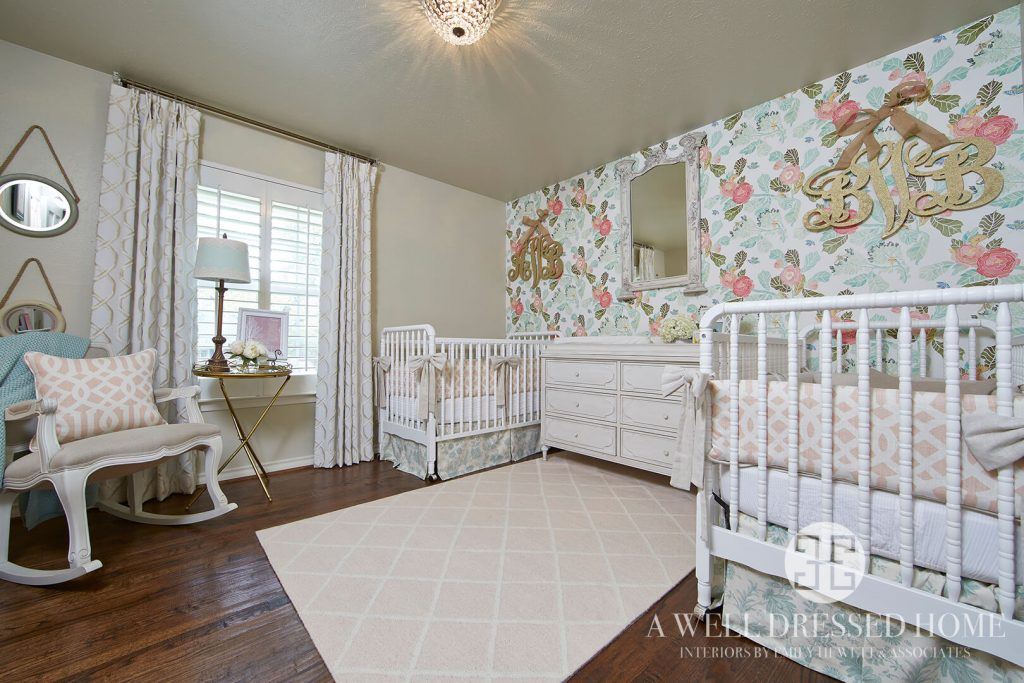Twin girl room with floral wallpaper and two white cribs.