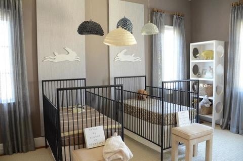 Twin nursery with two black cribs with bunny cutouts above each crib leaping towards each other.
