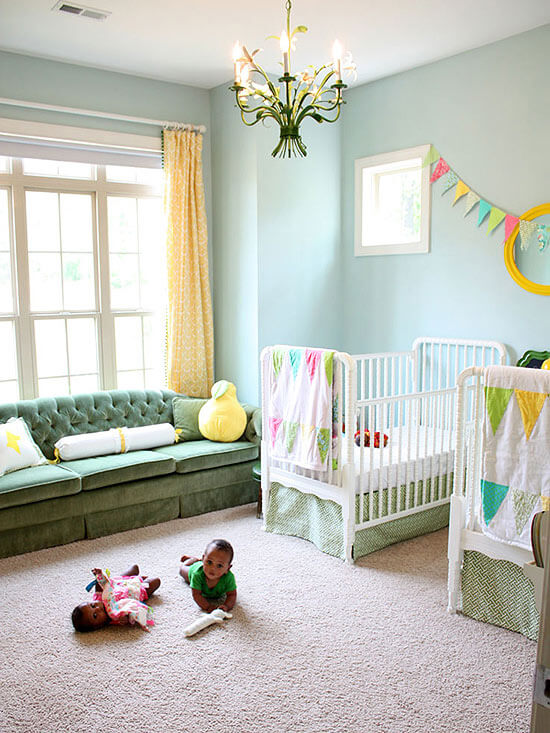 Twin nursery that's yellow and green with a dark green velvet couch in front of the window.
