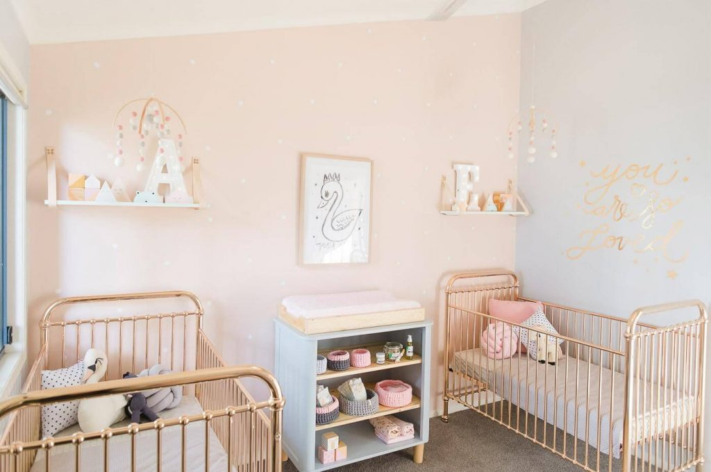 Twin girl nursery room with pink and gold accents and swans.
