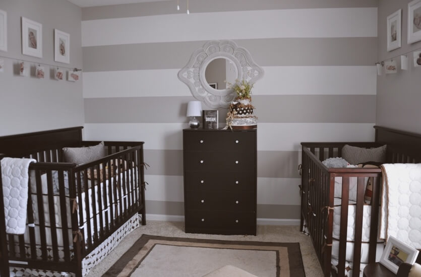 Gender neutral twin nursery with gray and white striped accent wall.