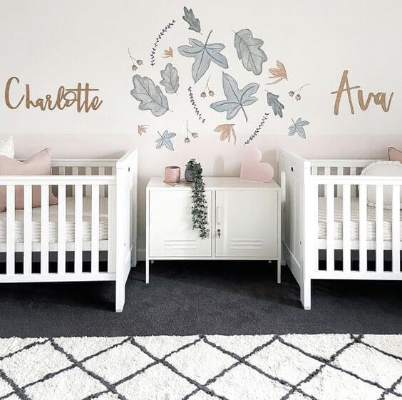 Twin girl baby room with two white cribs and a gray leaf decal between the two cribs.