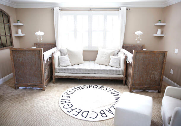 Gender neutral twin nursery with a round alphabet rug in between two brown cribs.