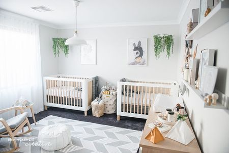 Gender neutral twin nursery with hanging garlands above the cribs.