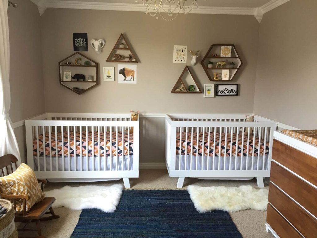 Gender neutral twin nursery with white cribs and colorful sheets.