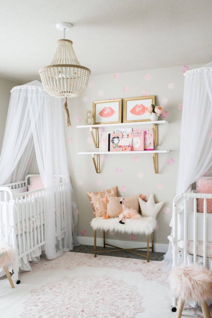 Classic pink and gold twin girl nursery with white cribs.