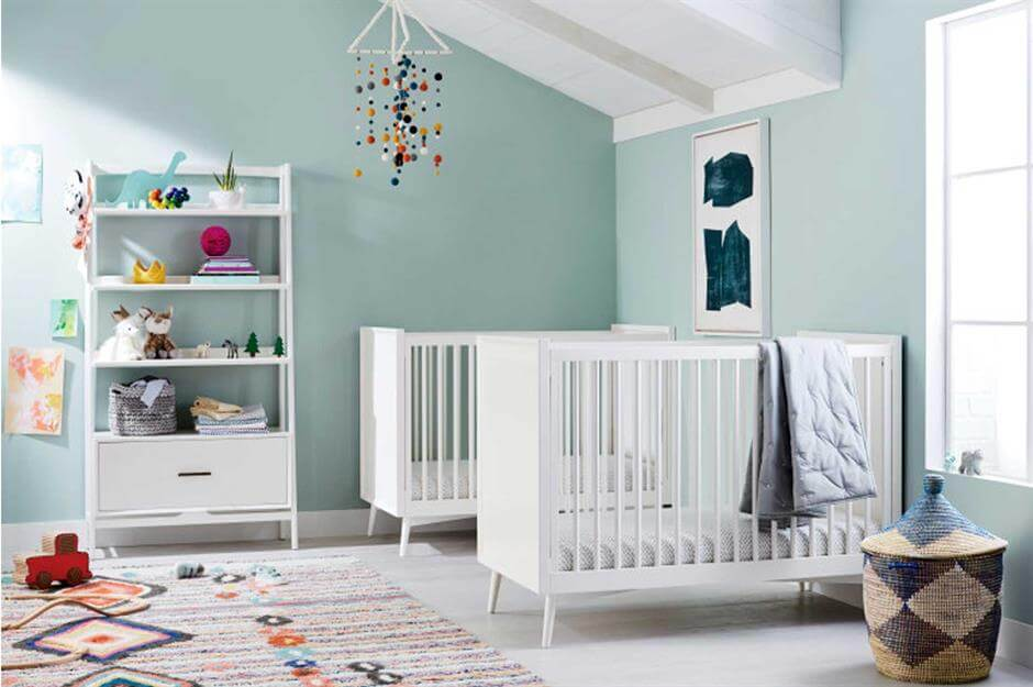 Colorful twin nursery with white cribs and mint green walls and a vibrant rug.