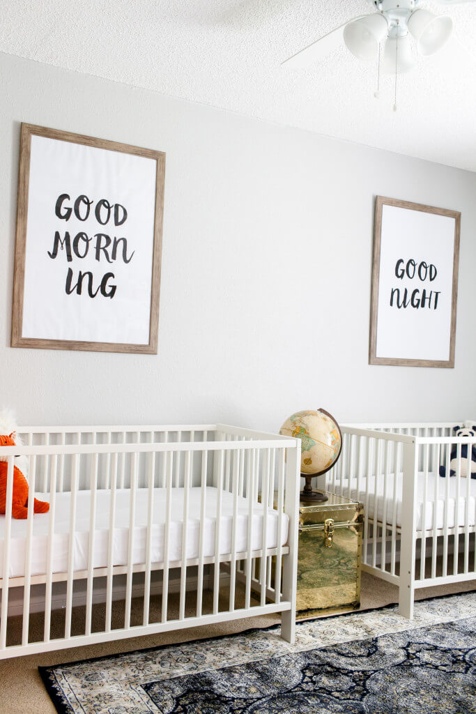 "Gender neutral twin nursery with ""good morning"" and ""good night"" signs hanging above white cribs."