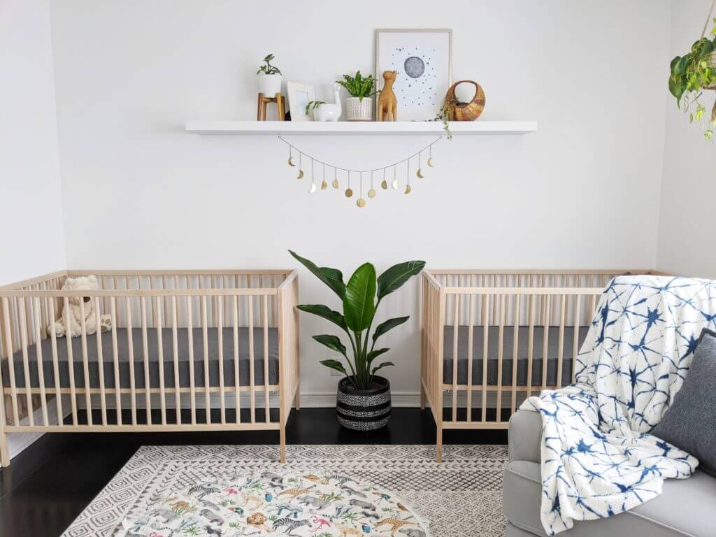 Gender neutral twin nursery with natural wood cribs and a colorful rub.
