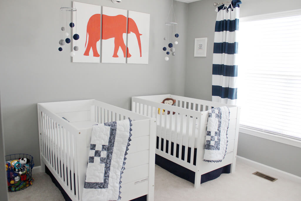 Twin boy nursery with navy blue and orange accents.