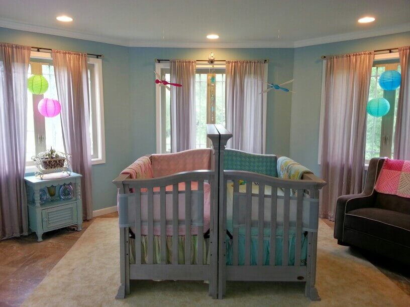 Girl boy twin nursery two cribs pushed together.