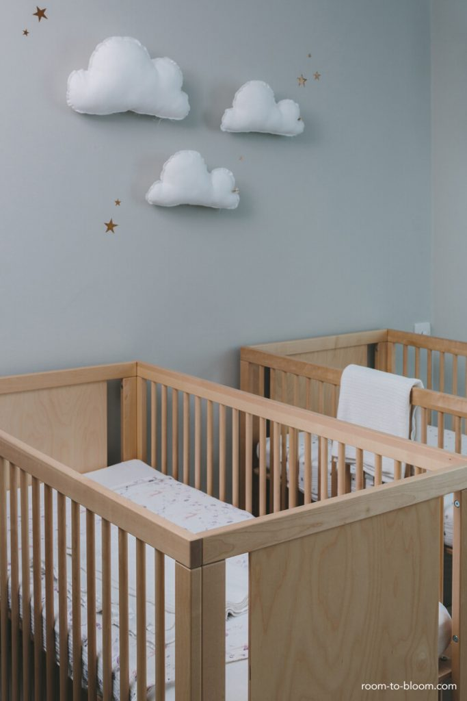 Gender neutral twin nursery with natural wood cribs and cloud wall hangings.