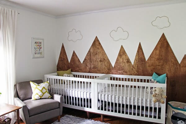 Gender neutral twin nursery with mountain wall mural painted behind cribs.