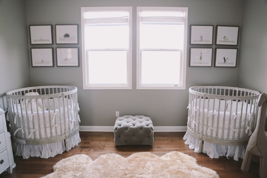Gender neutral twin nursery with round cribs.