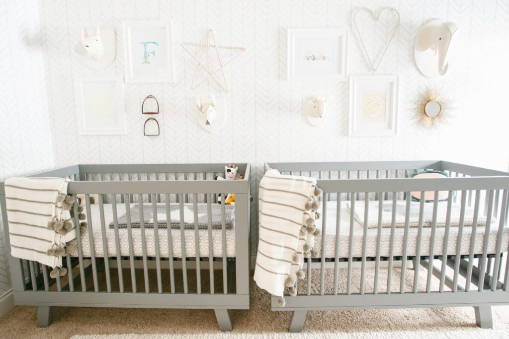 Gender neutral twin nursery with gray cribs.